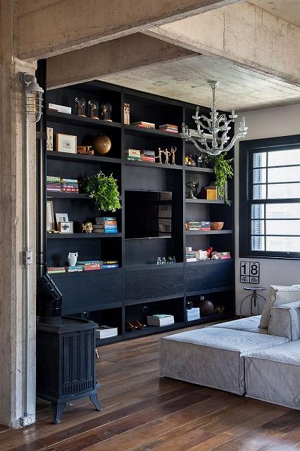 Large-open-bookshelf-in-dark-wood-anchors-the-light-filled-living-room.jpg