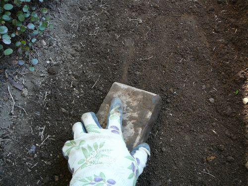 土をレンガで押し固める