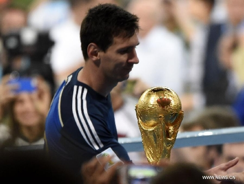 Within touching distance Messi walks past the World Cup trophy as he leads Argentina out
