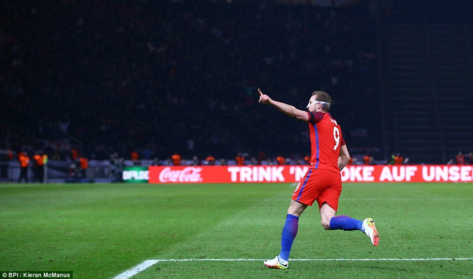 Harry Kane raises his arm in celebration of his 61st-minute goal shortly after beating Germany keeper Manuel Neuer