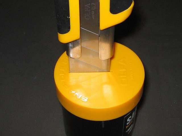オルファ 安全刃折処理器ポキ 133K にオルファ カッター ハイパー H 型 オートロック 212B(特大 H 刃)を差し込んだところ