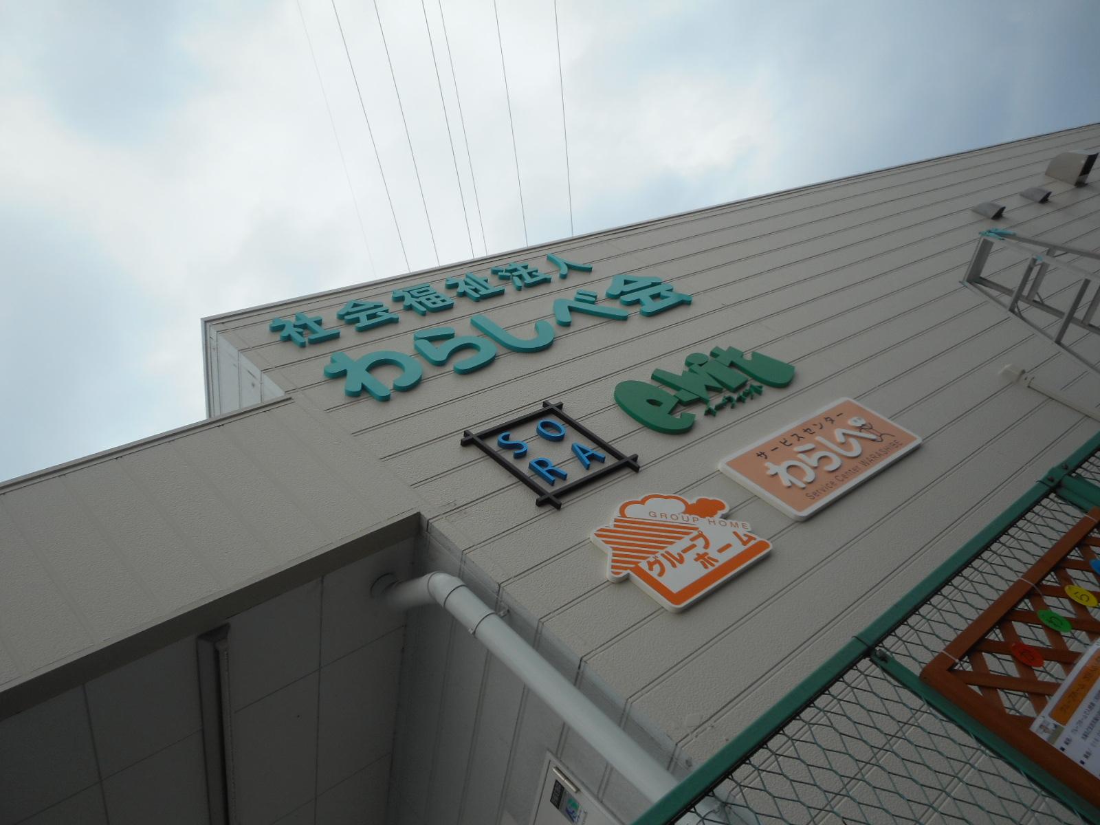 横からの写真。上から社会福祉法人わらしべ会、そら、イーウィット、グループホーム、サービスセンターわらしべのロゴ